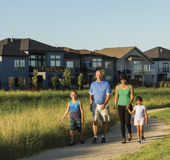Family walking on trails with houses in background